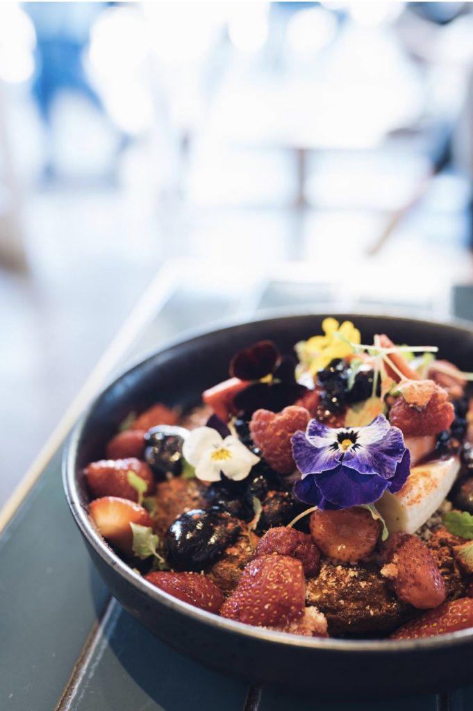Ricotta Hotcake topped with chocolate sauce, fresh berries, mascarpone, banana and edible flowers