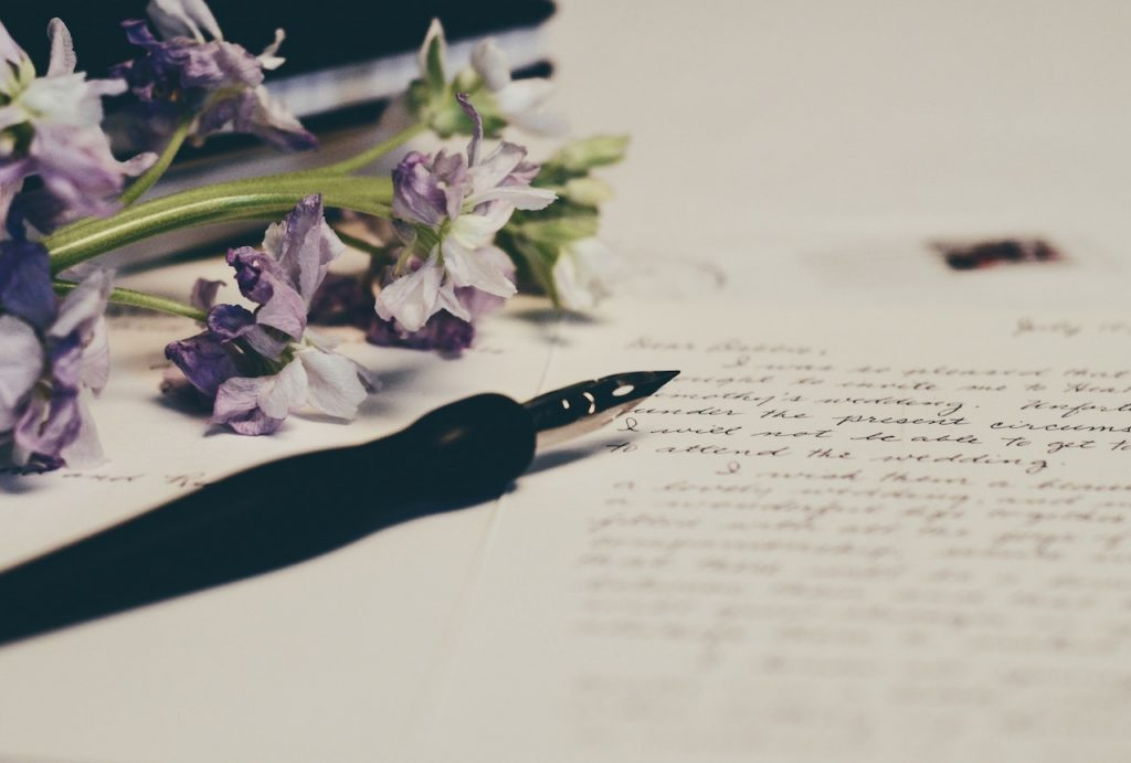 A black pen sits on top of a personalised letter next to some purple flowers