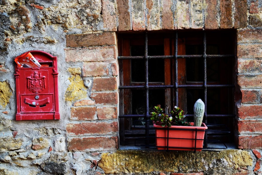 Red postal box on brick wall next to window with planter box and flowers