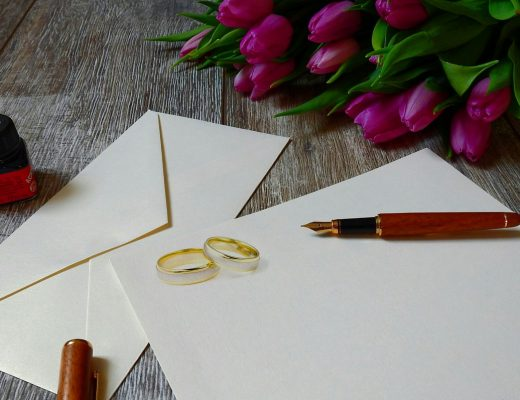 wedding rings on invitation with tulips and pen