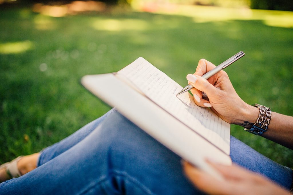 Writing notes outside with green grass background